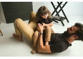 父亲和年幼的儿子在家里的起居室里玩耍年_12699679