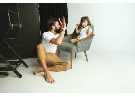 父亲和年幼的儿子在家里的起居室里玩耍年_13341328