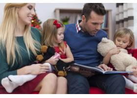 爸爸在圣诞节给他的小女儿们读书_10677095
