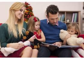 爸爸在圣诞节给女儿们读书_10677061