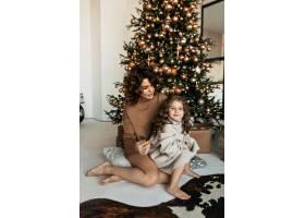 留着卷发的迷人母女俩在家中白色室内圣诞树_11146208