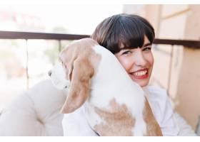 深棕色头发的微笑女孩抱着比格犬的特写户外_10562421