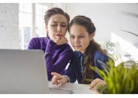 漂亮的女孩坐在家里打开的便携式电脑前用_10897831