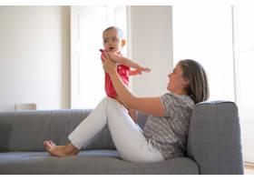 漂亮的母亲坐在沙发上抱着她的小女儿跪着_11622997