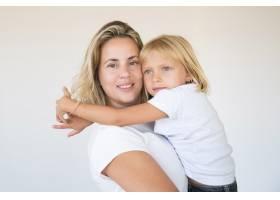 漂亮的金发妈妈抱着女儿看着相机_11076347