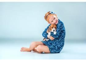 灰墙上快乐的女孩和一只小猎犬_7540143