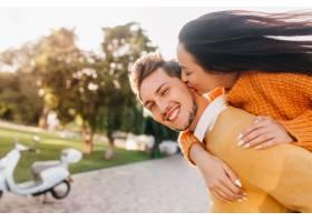 热情洋溢的白指甲女子亲吻橙色装扮的大笑男_10787488