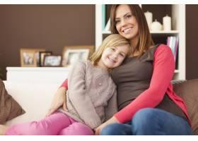 慈爱的母亲和女儿坐在沙发上的肖像_11100943