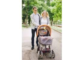 父亲和年轻的母亲推着手推车带着她的孩子在_1011747