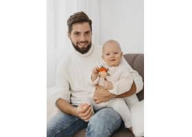 英俊的父亲带着孩子在沙发上摆姿势_11904619