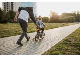 父亲教他的儿子如何骑自行车_11176357