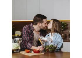 父女俩在厨房做饭时接吻的前景_11765745