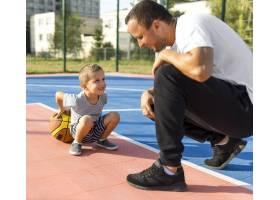 父子俩一起在篮球场上玩耍_11176293