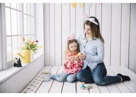 戴着兔子耳朵的小女孩和妈妈为复活节画彩蛋_3831232