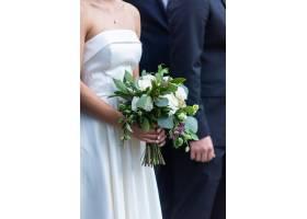 身着漂亮白色婚纱的新娘手持新娘花束站在新_11342923