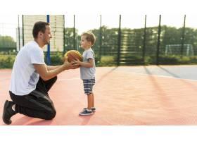 父子俩在篮球场上远眺_11176297