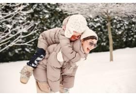 身穿棕色夹克的女子与女儿在雪地公园的特写_13181664