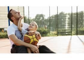 父子俩坐在篮球场上_11176294