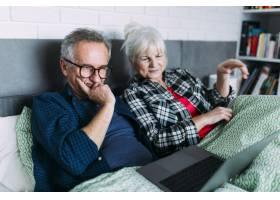 躺在床上看笔记本电脑的老年夫妇_2284870