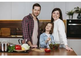 父母和女儿在厨房摆姿势的前景_11765735