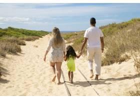 父母和孩子穿着夏装沿着沙路走向大海女_11072773