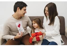 父母在家中带着女儿和礼物的前景_11904698