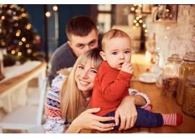 父母带着他可爱的儿子在圣诞摄影_10895773