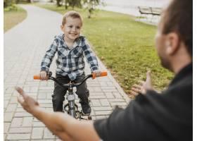 爸爸教他的孩子如何骑自行车_11176358