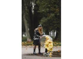 雨天公园里的一家人穿着黄色雨衣的孩子和_11154987