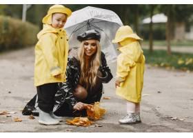 雨天公园里的一家人穿着黄色雨衣的孩子和_11154996