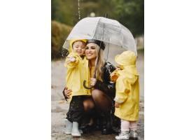 雨天公园里的一家人穿着黄色雨衣的孩子和_11154998