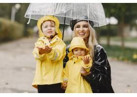 雨天公园里的一家人穿着黄色雨衣的孩子和_11155000