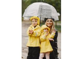 雨天公园里的一家人穿着黄色雨衣的孩子和_11155004