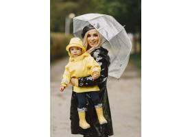 雨天公园里的一家人穿黄色雨衣的孩子和穿_11154983