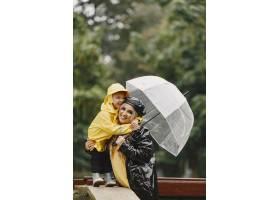 雨天公园里的一家人穿黄色雨衣的孩子和穿_11154986