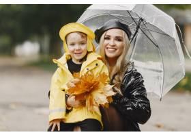 雨天公园里的一家人穿黄色雨衣的孩子和穿_11154992