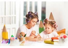 这位年轻的母亲和她的小女儿在家里用铅笔作_11315578