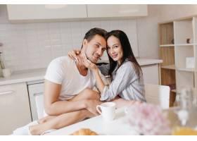 迷人的年轻女子坐在男友的膝盖上喝咖啡_10785898