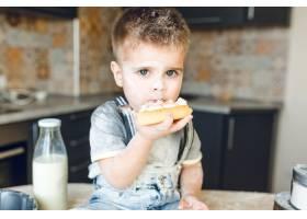 有趣的孩子坐在厨房桌子上吃蛋糕的特写镜头_9860768
