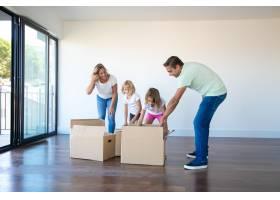 高加索父母和女儿在带阳台的空房间里打开纸_10579233