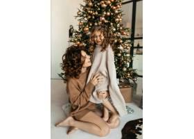 年轻漂亮的母亲和小女儿穿着针织衣服在圣诞_11146239