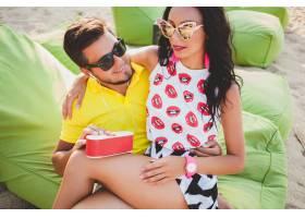 年轻漂亮的潮人情侣坐在沙滩上听着音乐_11083347