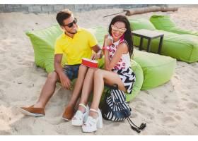 年轻漂亮的潮人情侣坐在海滩上听着音乐_11083345