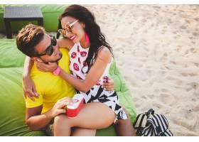 年轻漂亮的潮人情侣坐在海滩上听着音乐_11083357