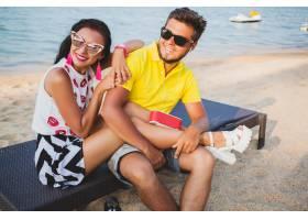 年轻漂亮的潮人情侣坐在海滩上听着音乐_11083361