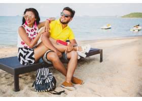 年轻漂亮的潮人情侣坐在海滩上听着音乐_11083366