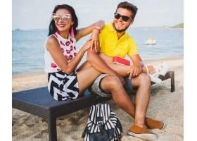 年轻漂亮的潮人情侣坐在海滩上听着音乐_11083367