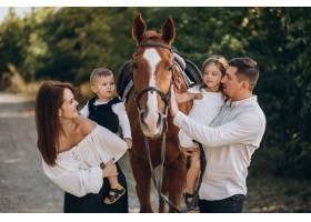 年轻的家庭带着孩子在森林里与马玩耍_10703714