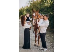 年轻的家庭带着孩子在森林里与马玩耍_10703770