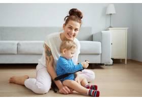年轻的母亲和她一岁的小儿子穿着睡衣摆姿势_10271296